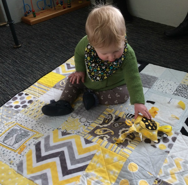 Baby playing on Taggie Blanket